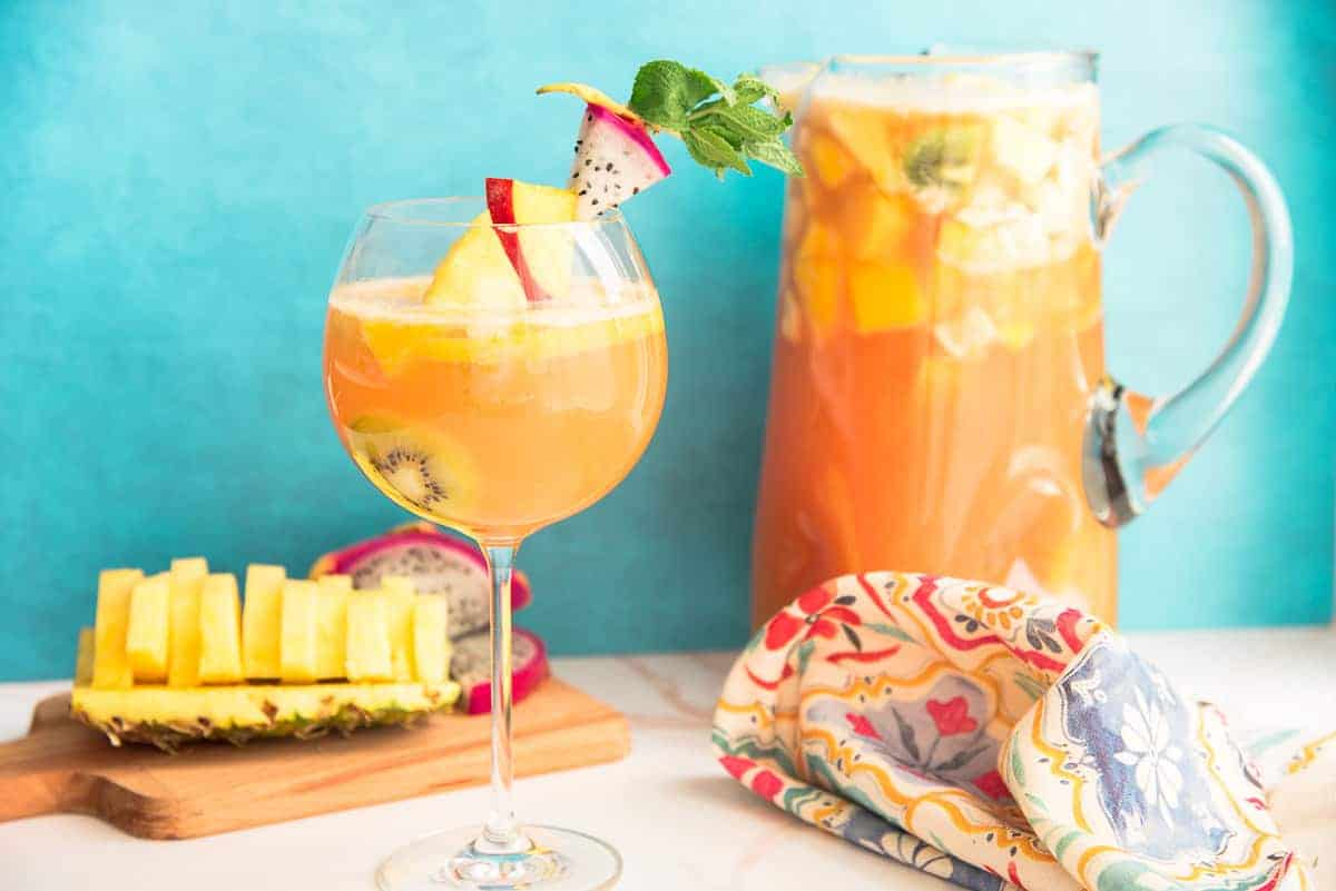 Preview image of a wine goblet of Tropical Sangria next to a wooden cutting board with pineapple and dragonfruit and a glass pitcher of sangria.