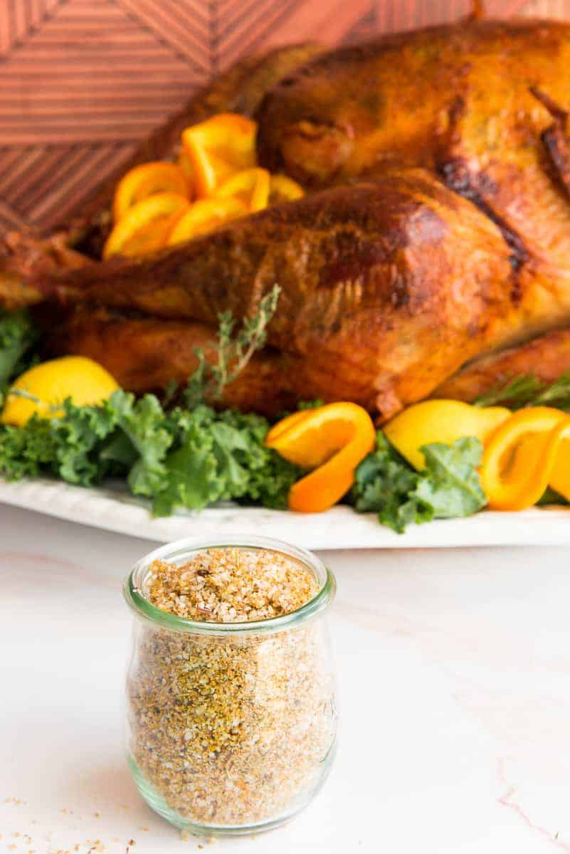 Portrait image of a clear glass jar of Citrus-Herb Dry Brine in front of a roast turkey on a white platter garnished with greens.