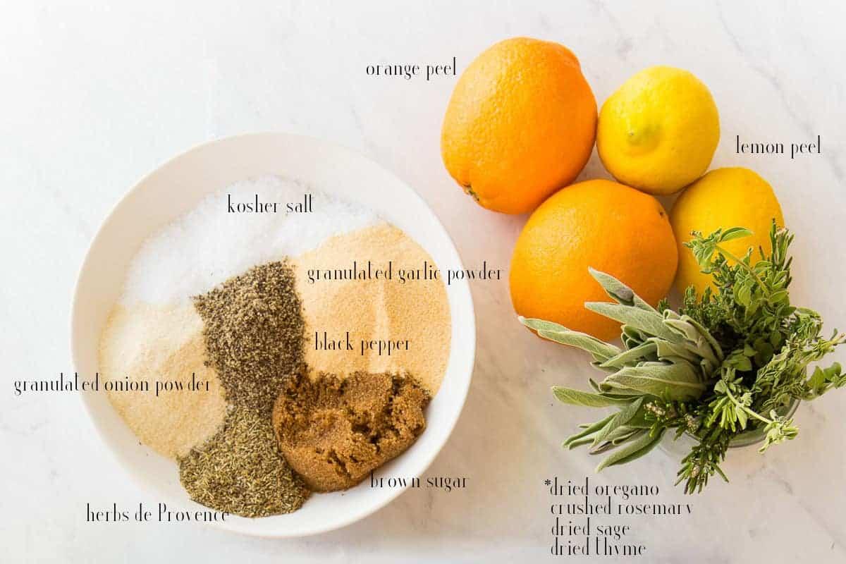 Ingredients needed to make Citrus-Herb Dry Brine on a white surface: salt, garlic powder, onion powder, pepper, brown sugar, herbs de Provence, orange peel and lemon peel. Fresh herbs shown for additional options.