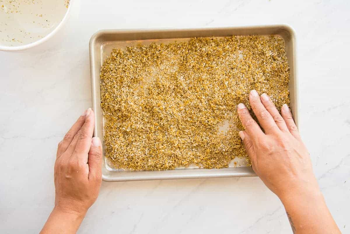 Hands smooth the Citrus-Herb Dry Brine into an even layer on a sheetpan before allowing it to dry out.