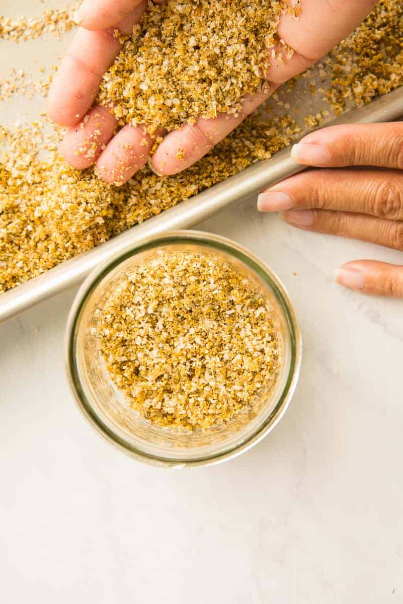 A hand transfers the dried out Citrus-Herb Dry Brine to a clear glass jar from the silver sheetpan