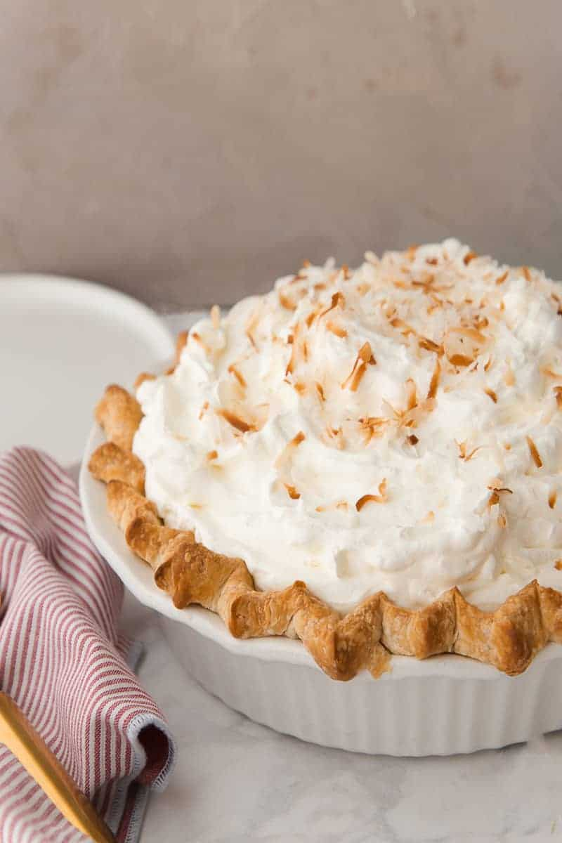 Coconut rum cream pie in a white ceramic pie dish garnished with toasted coconut flakes.