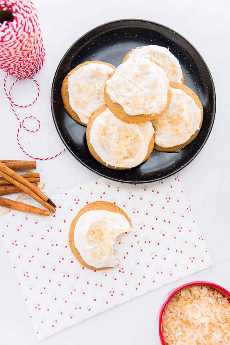 Coquito cookies with coquito buttercream frosting on a black plate. One cookie has a bite taken from it.