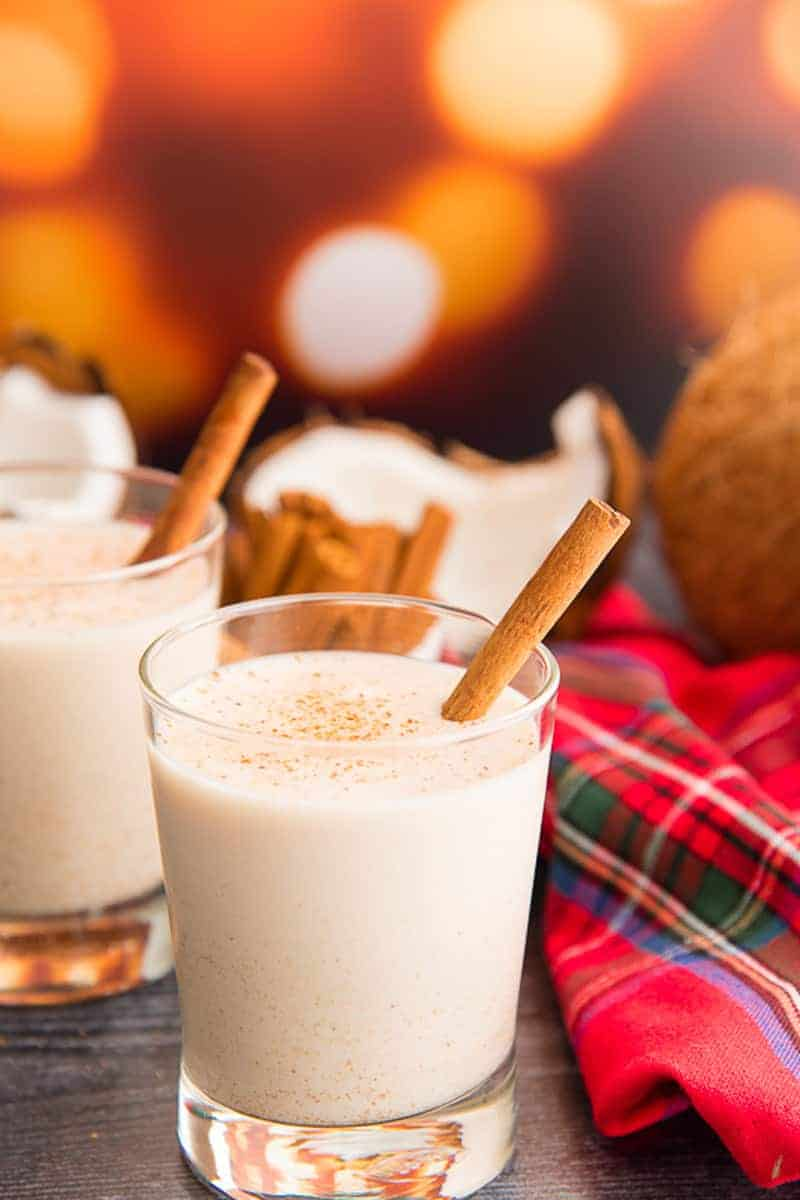 Lead image for Coquito Recipes. Two glasses of coquito garnished with cinnamon sticks next to a plaid napkin.