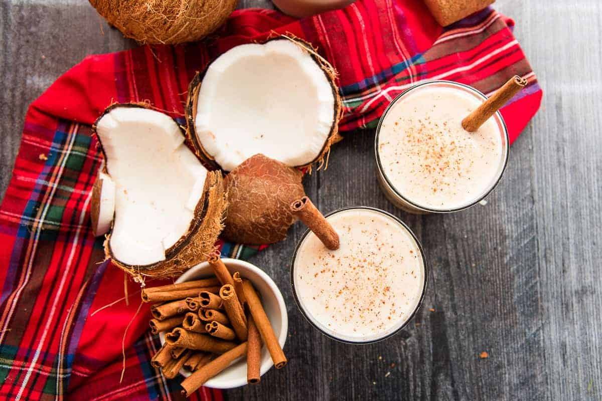 Final image overhead view of two glasses garnished with cinnamon sticks next to a cracked open coconut.