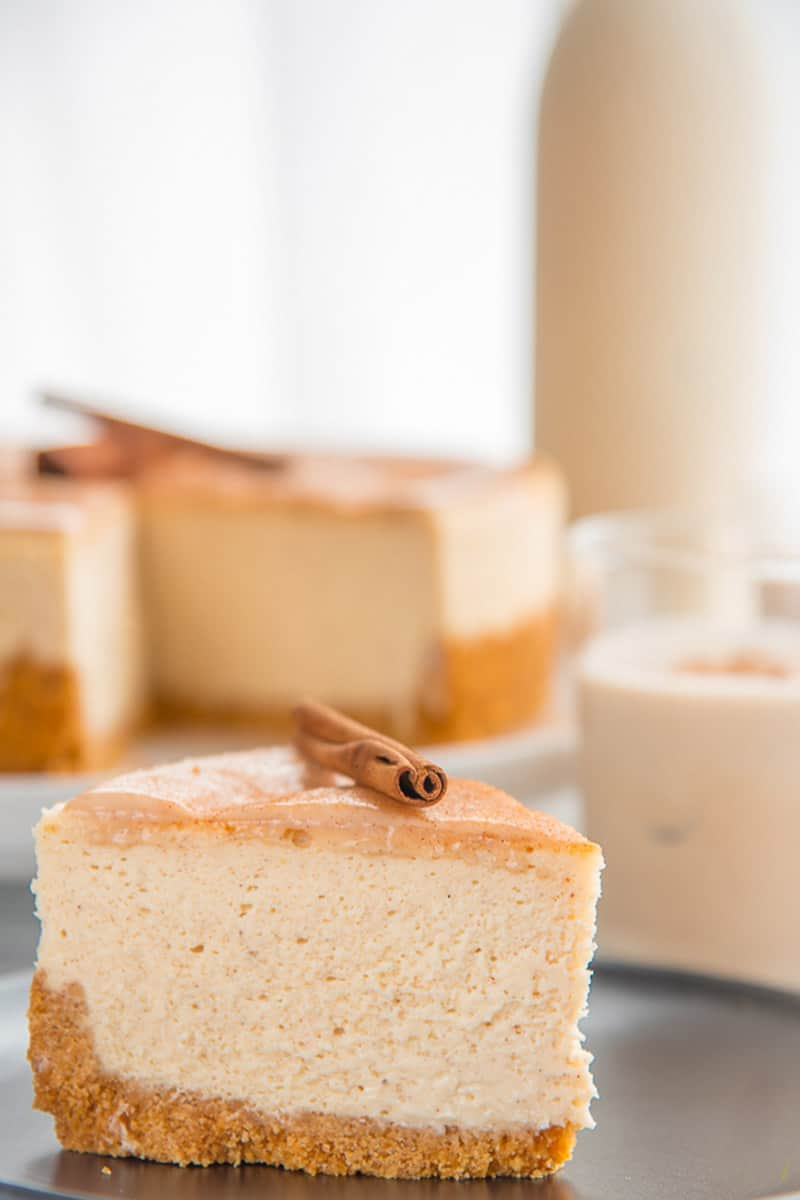 Slice of Coquito Cheesecake on a dark plate in front of a bottle of coquito. Two coquito recipes in one.