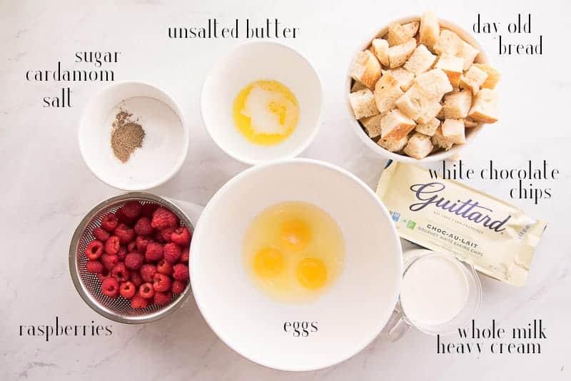 The ingredients needed for Raspberry White Chocolate Bread Pudding: sugar, cardamom, salt, unsalted butter, day old bread. white chocolate chips, whole milk, heavy cream, eggs, and raspberries