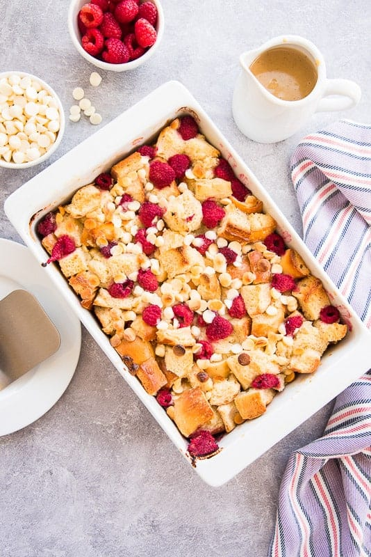 Overhead portrait image of a white dish of Raspberry White Chocolate Bread Pudding surrounded by bowls of raspberries, white chocolate chips and a pitcher of sauce