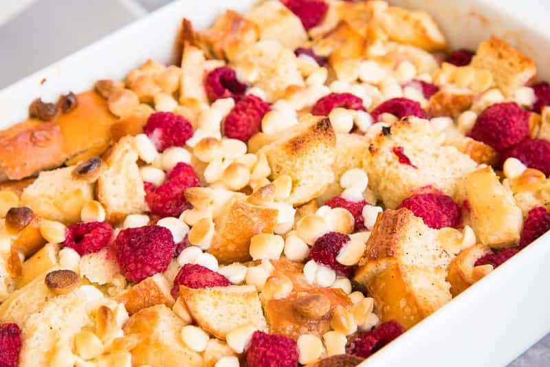 Close up of the baked Raspberry White Chocolate Bread Pudding in a white baking dish