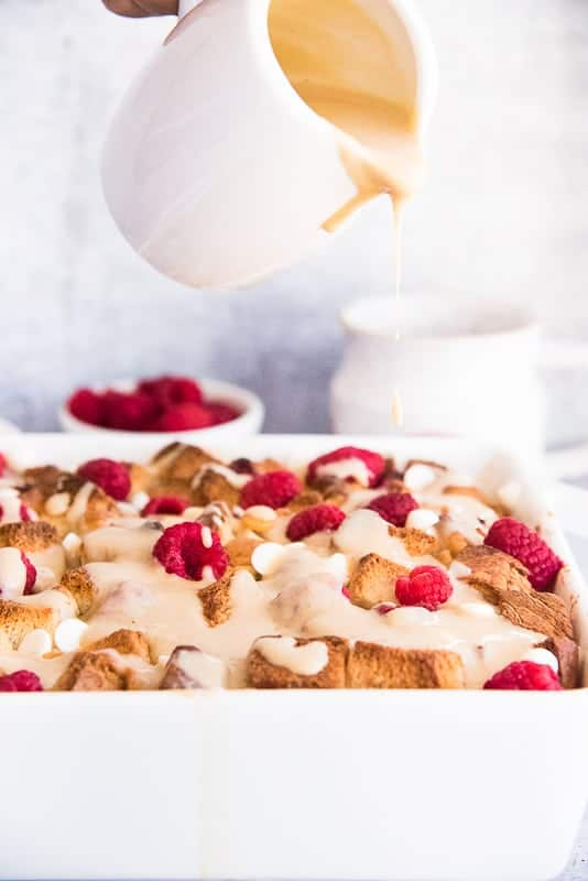 Amaretto cream sauce is poured from a small white pitcher onto the baked Raspberry White Chocolate Bread Pudding