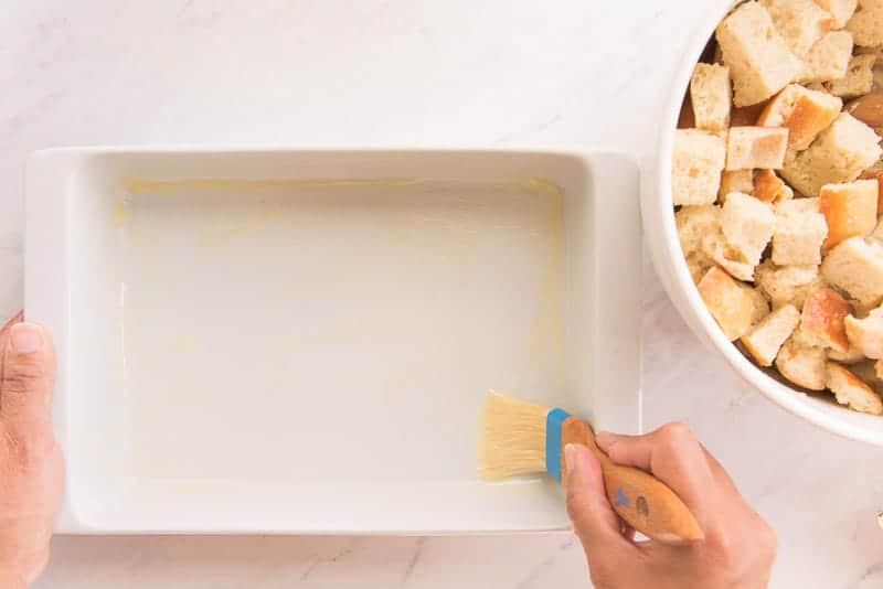A hand uses a pastry brush to grease a white rectangular baking dish with melted butter