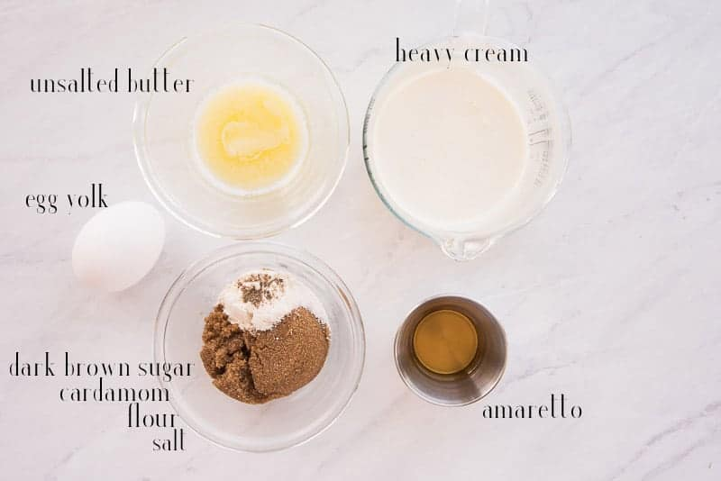 Ingredients to make amaretto cream sauce on a white surface: unsalted butter, heavy cream, amaretto, dark brown sugar, salt, cardamom, flour, and egg yolk