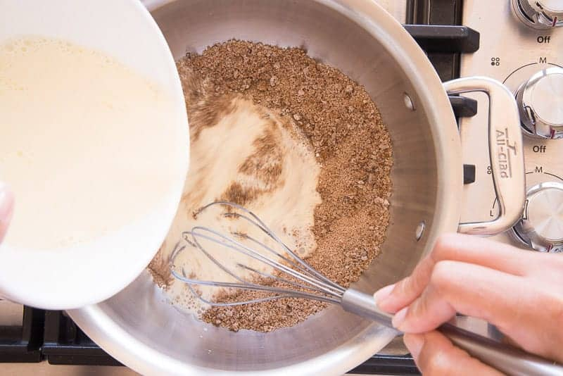 The egg and cream mixture is added to the butter, sugar and flour mixture with a silver whisk