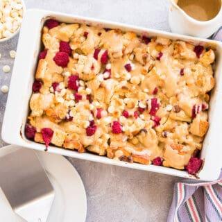 Overhead horizontal image of a white baking dish with Raspberry White Chocolate Bread Pudding. Bowls of raspberries, white chocolate chips, and a pitcher of amaretto cream sauce around the dish.