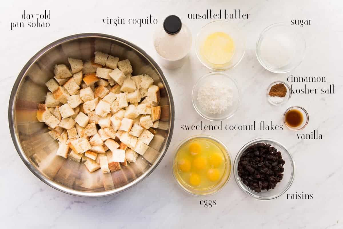 The ingredients to make Coquito Bread Pudding on a white counter: stale pan sobao, virgin coquito, unsalted butter, sugar, cinnamon, kosher salt, vanilla, raisins, eggs, sweetened coconut flakes.