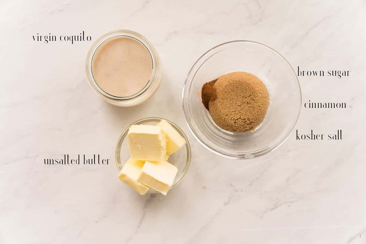 The ingredients to make the Coquito Toffee Sauce on a white countertop: virgin coquito, brown sugar, cinnamon, kosher salt, and unsalted butter.