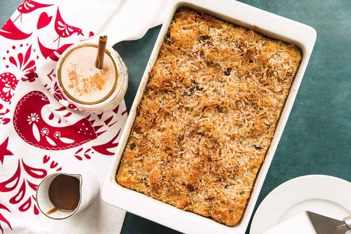 The baked Coquito Bread Pudding in a white baking dish on a green surface next to a white kitchen towel with red artwork.