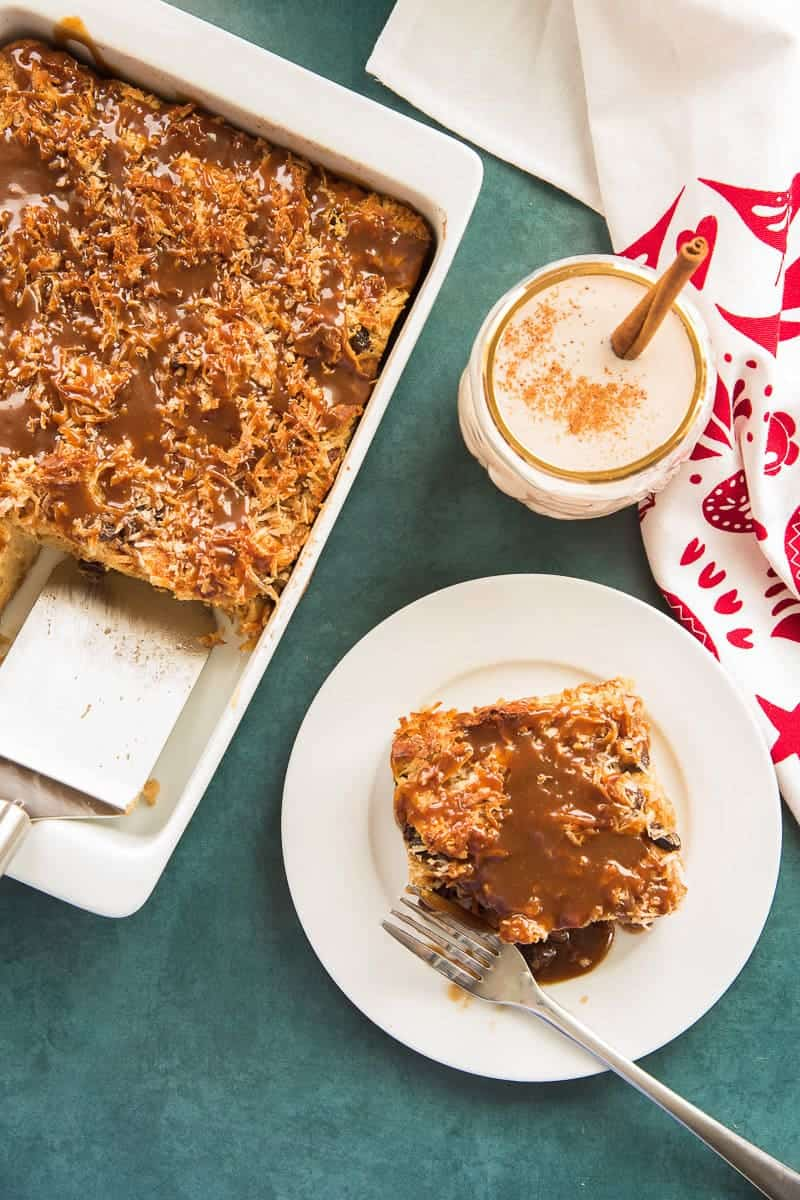 Overhead portrait image white plate with a square serving of Coquito Bread Pudding with sauce below a glass of coquito garnished with a cinnamon stick. To the left is the white baking dish with the remaining Budin de Coquito