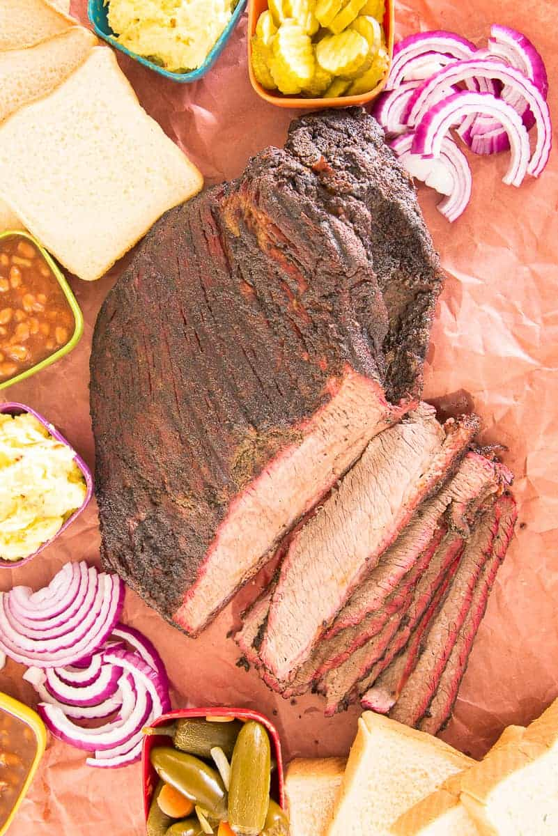 Lead image of Coffee-Rubbed Smoked Brisket on a sheet of peach butcher paper surrounded by sides and condiments.