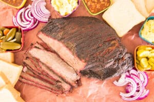 The sliced coffee-rubbed smoked brisket overhead shot surrounded by condiments and sides