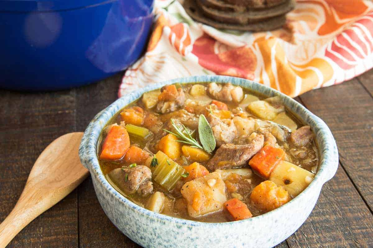 Horizontal image of a blue speckled bowl of Harvest Pork Stew next to a wooden soup spoon