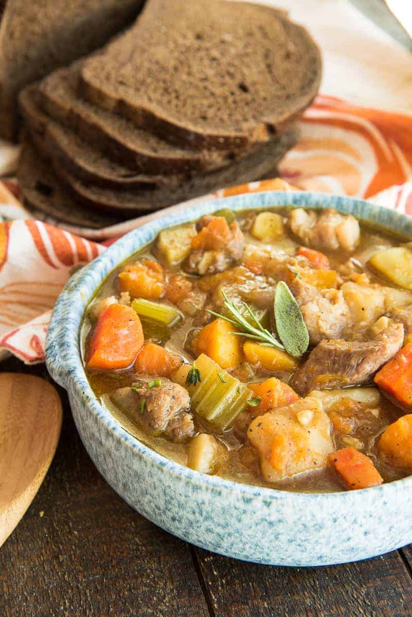 Portrait image of a close-up shot of the Harvest Pork Stew in a blue-speckled bowl. A loaf of pumpernickel bread is sliced in the background.