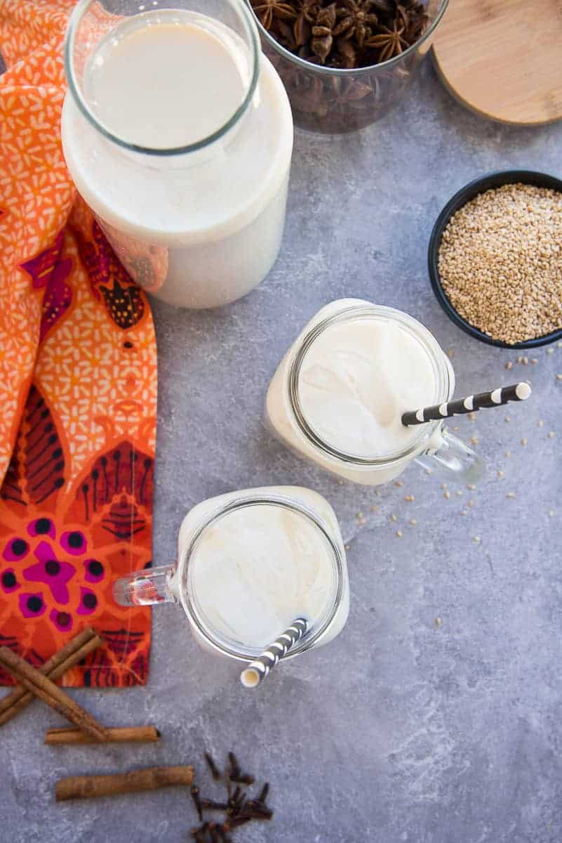 Portrait image of a carafe of Sesame Seed Milk (Horchata de Ajonjolí) next to two glass mugs of horchata and a bowl of toasted sesame seeds.