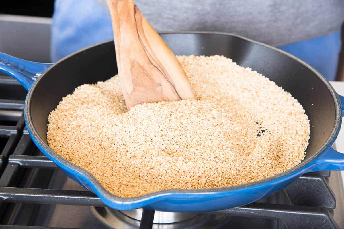 The sesame seeds are halfway toasted in a blue pan.