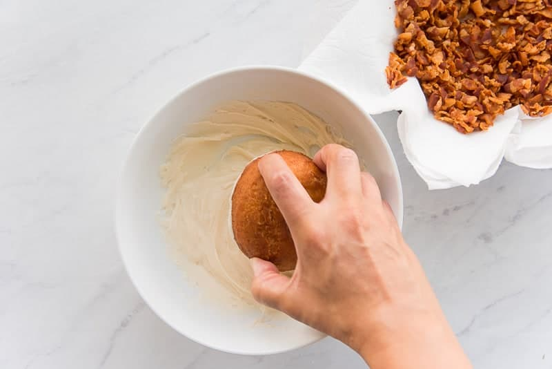 A hand dips a cake donut into the maple glaze in a white bowl.
