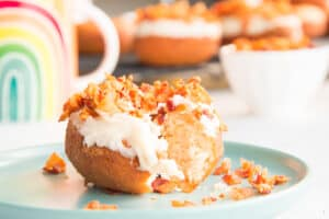 Preview image of a maple bacon donut with a bite removed on a teal plate.