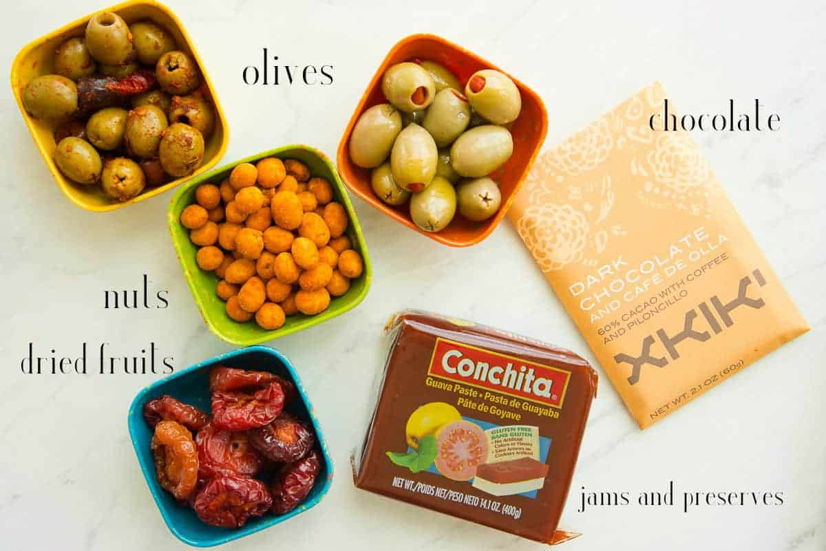 Condiments to add to the board on a white surface: two types of olives, Japanese nuts, guava paste, dried plums, chocolate.