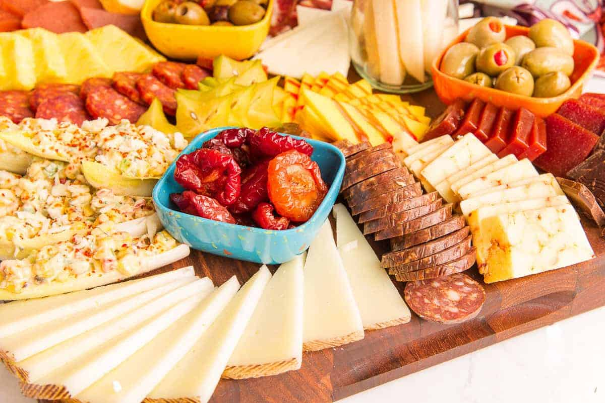 Many cheeses, fruits, and meats are shown in a horizontal image of a Mexican-Inspired Charcuterie Board