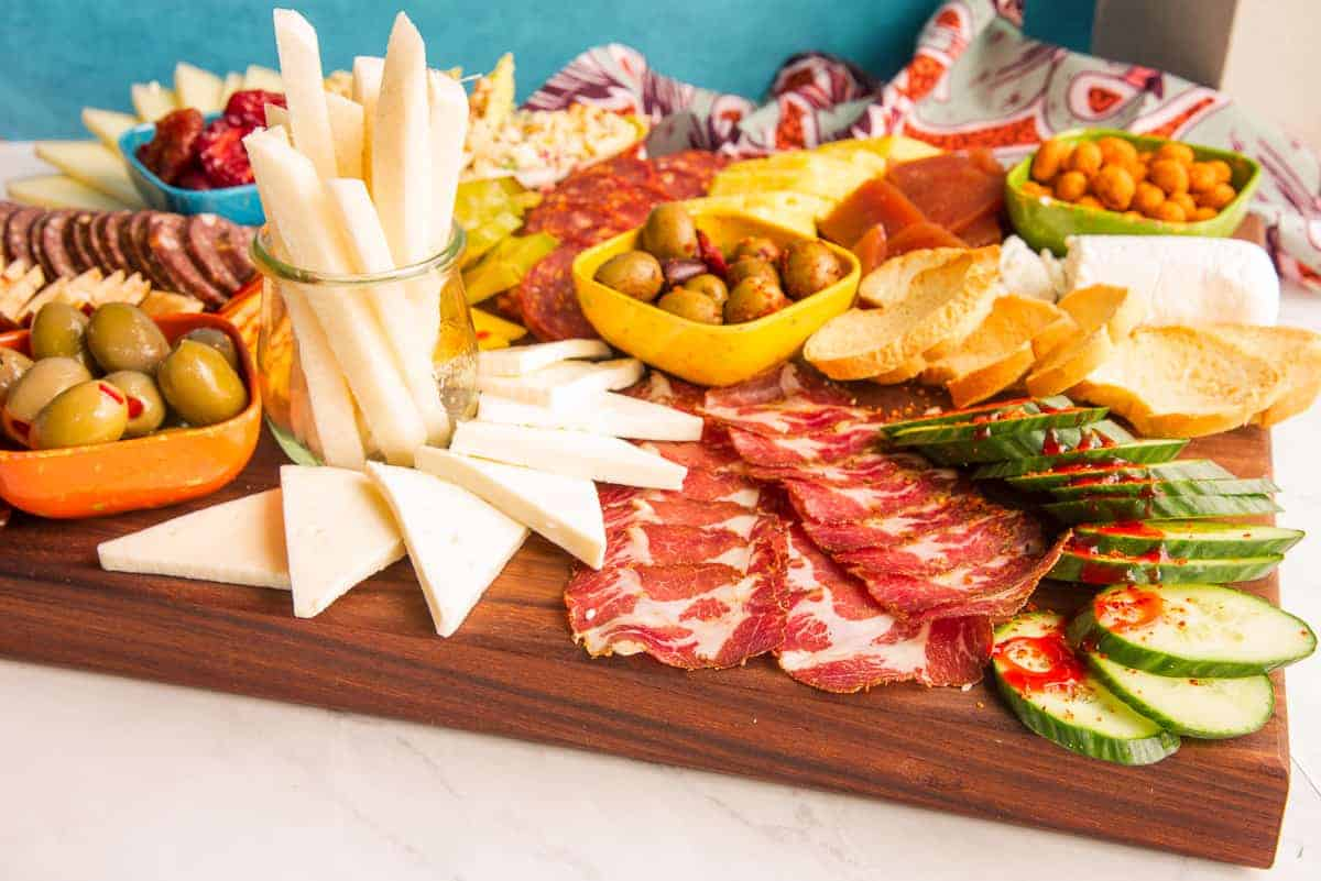 Horizontal image of a Mexican-Inspired Charcuterie Board on a dark wooden board