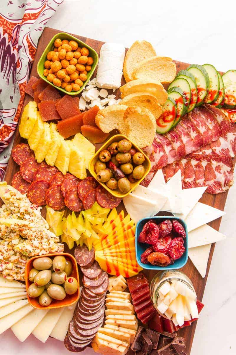 Portrait image of a Mexican-Inspired Charcuterie Board on a dark wooden surface