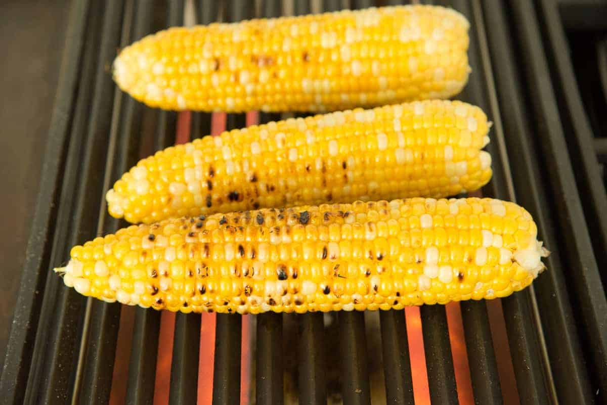 Corn is charred on a grill to make esquites.