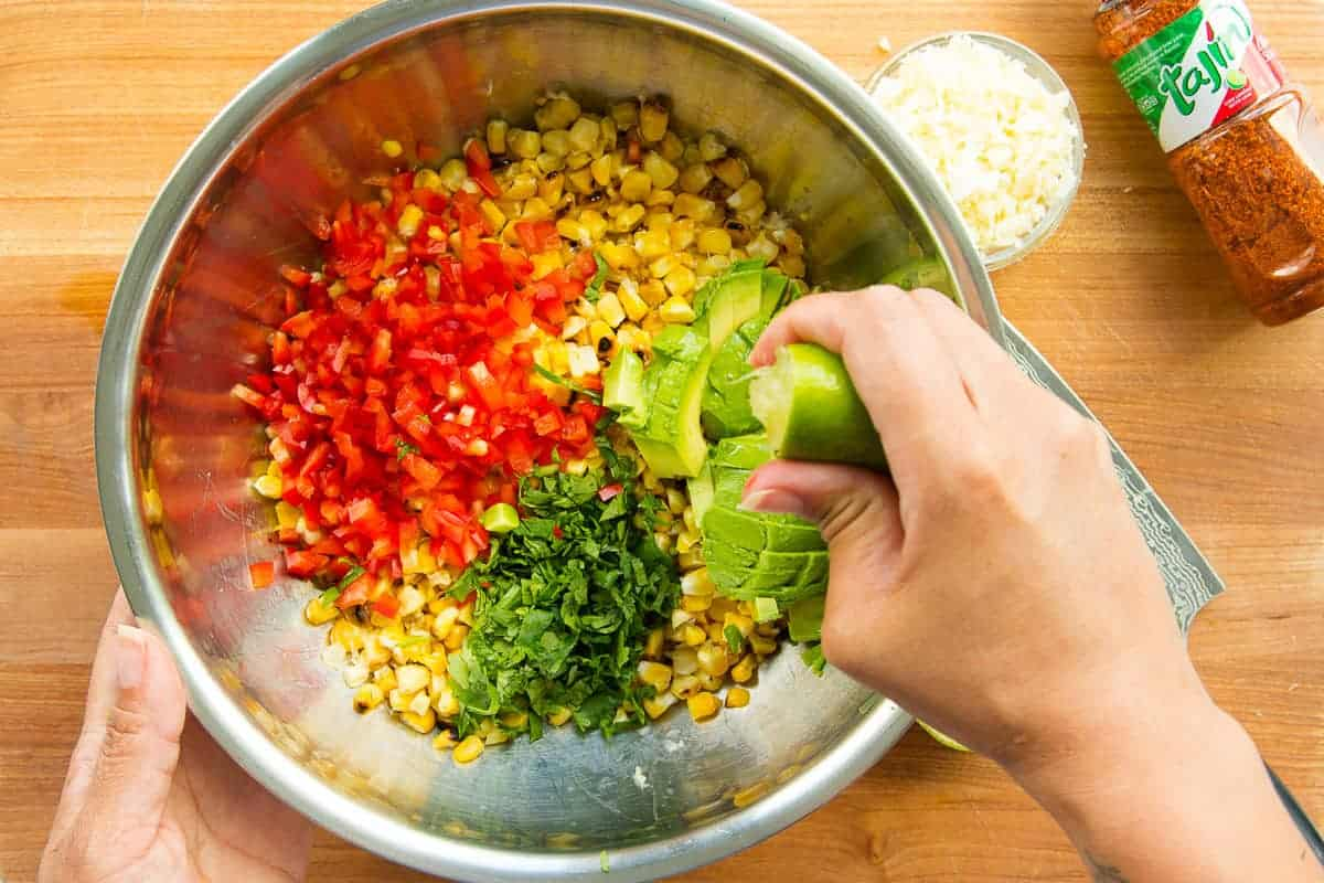 A hand squeezes juice from a lime into a bowl of ingredients to make esquites.