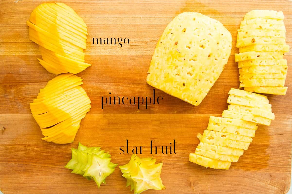 Mango, pineapple, and star fruit are sliced to add to the board