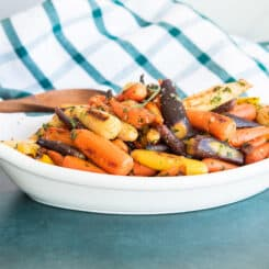 Preview image of a white, oblong bowl of Rainbow Carrots in Tarragon Brown Butter Sauce on a dark green surface.