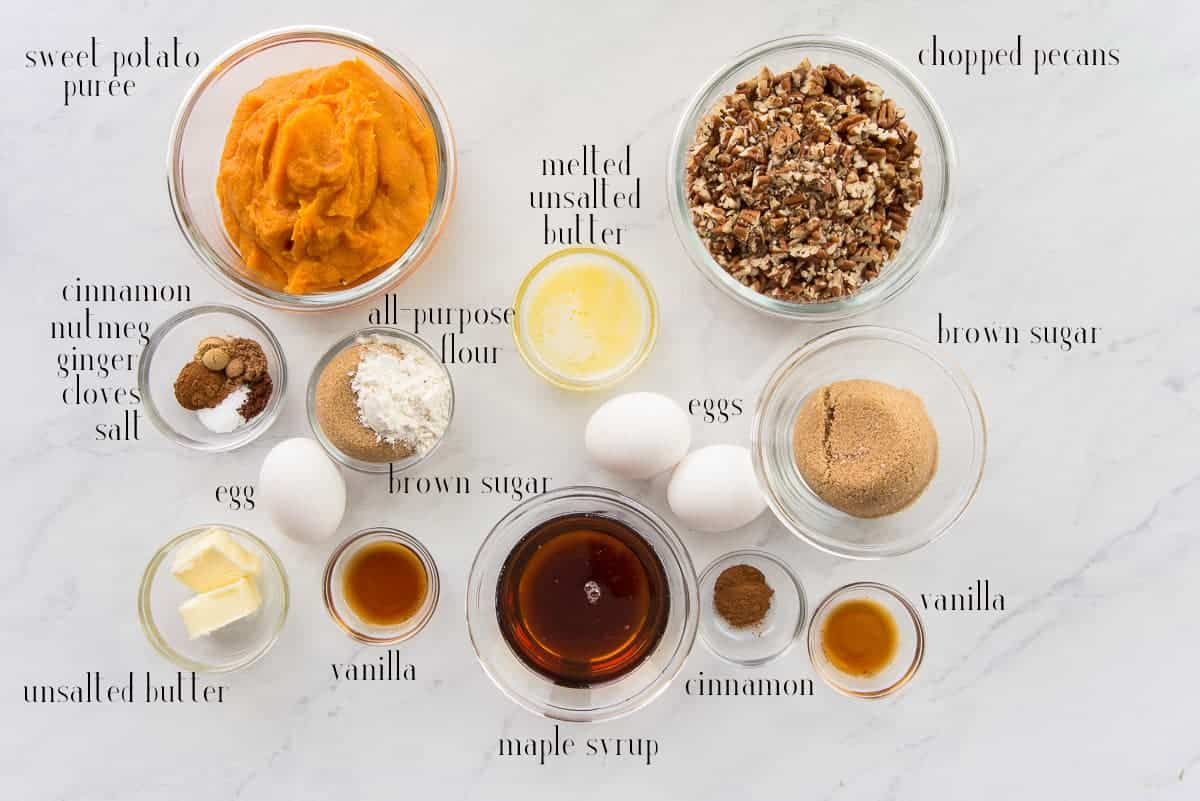 The ingredients to make Sweet Potato Maple Pecan Pie sweet potato puree, unsalted butter, chopped pecans, brown sugar, vanilla, cinnamon, eggs, maple syrup, flour, and spices.