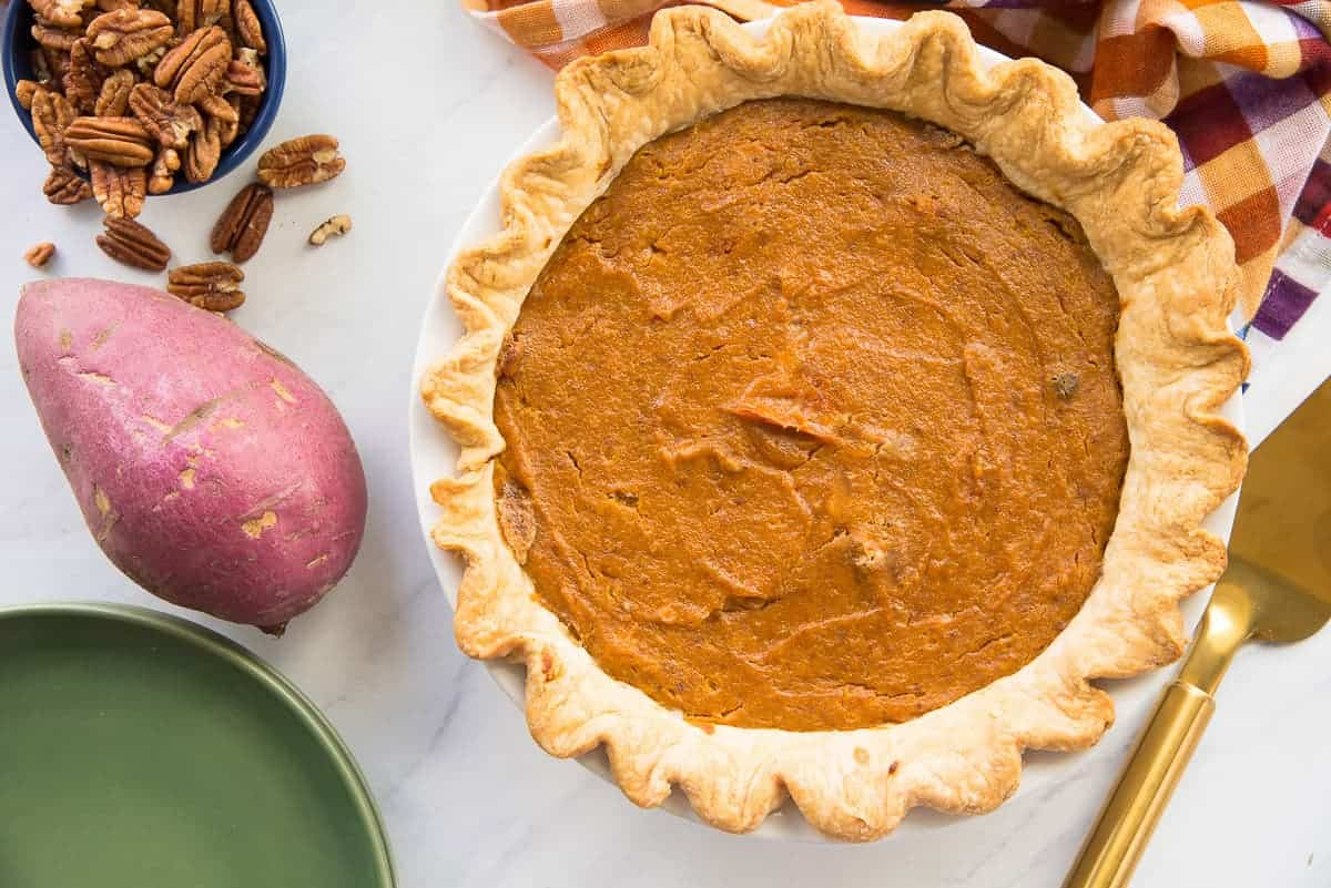 Horizontal image of the whole, baked Sweet Potato Maple Pecan Pie surrounded by a sweet potato and pecan halves