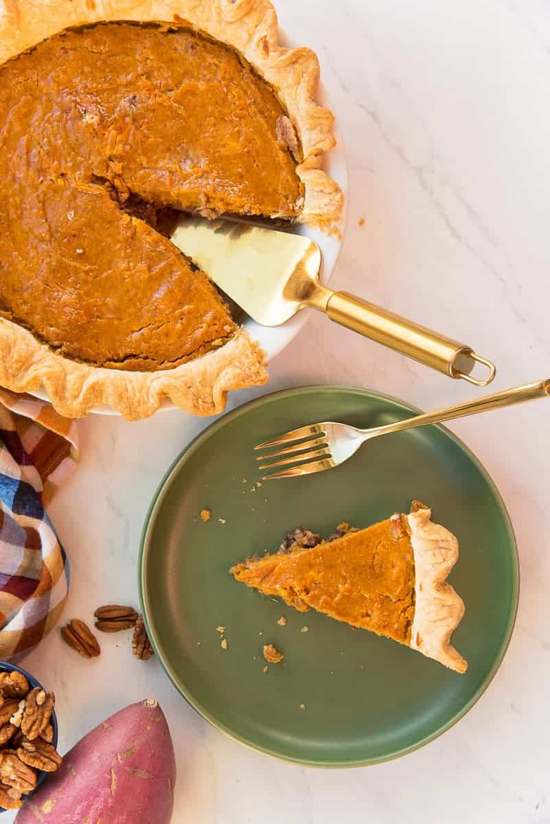 Overhead portrait image of a Sweet Potato Maple Pecan Pie with a slice removed and sitting on a green plate next to a gold fork.