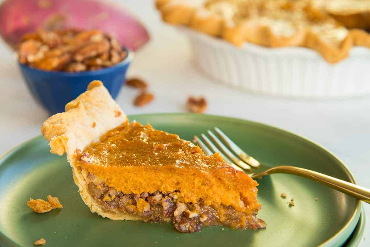 Horizontal image of a slice of Sweet Potato Maple Pecan Pie on a green plate. a gold fork rests on the plate to the right of the pie.