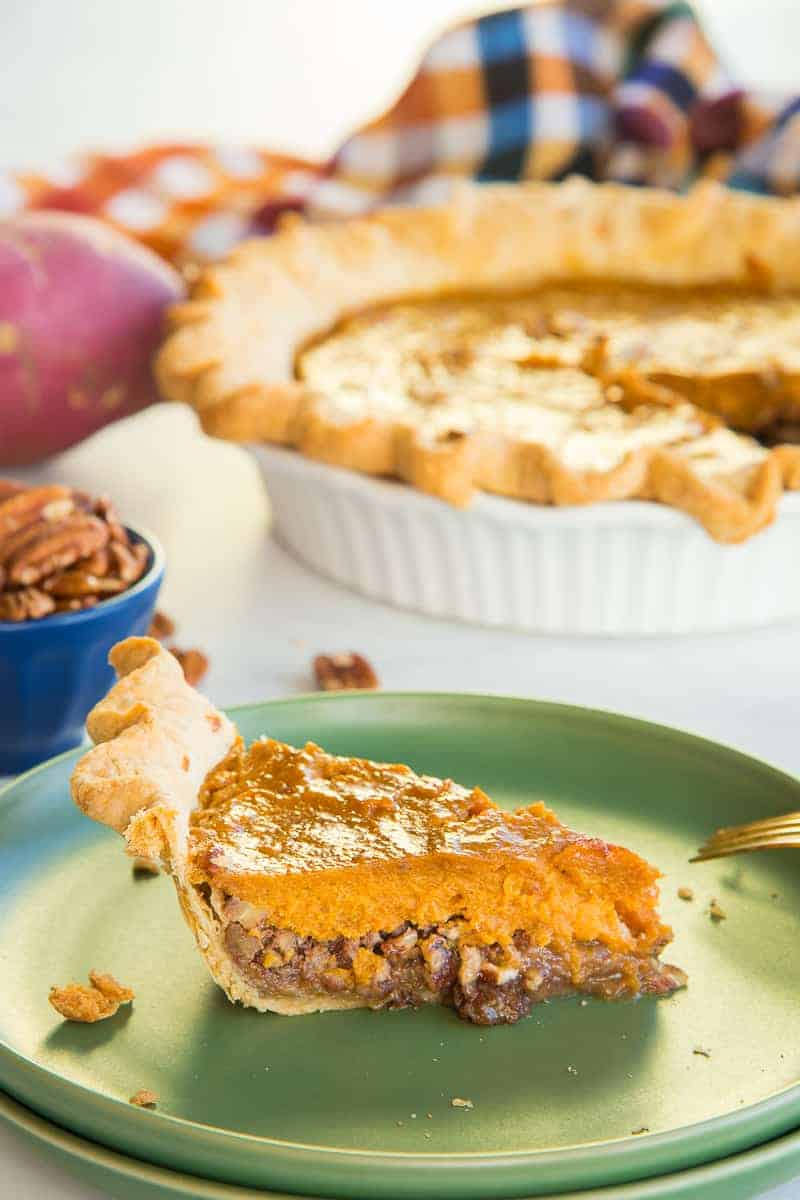 Lead image of a slice of Sweet Potato Maple Pecan Pie on a green plate in front of the rest of the pie