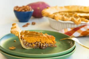 Preview image of a slice of Sweet Potato Maple Pecan Pie on a green plate. The rest of the pie is in the right background.