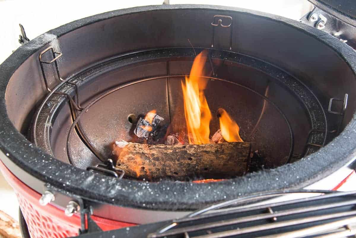 Post oak is added to the charcoal to create the smoke in the bottom of a kamado-style smoker.