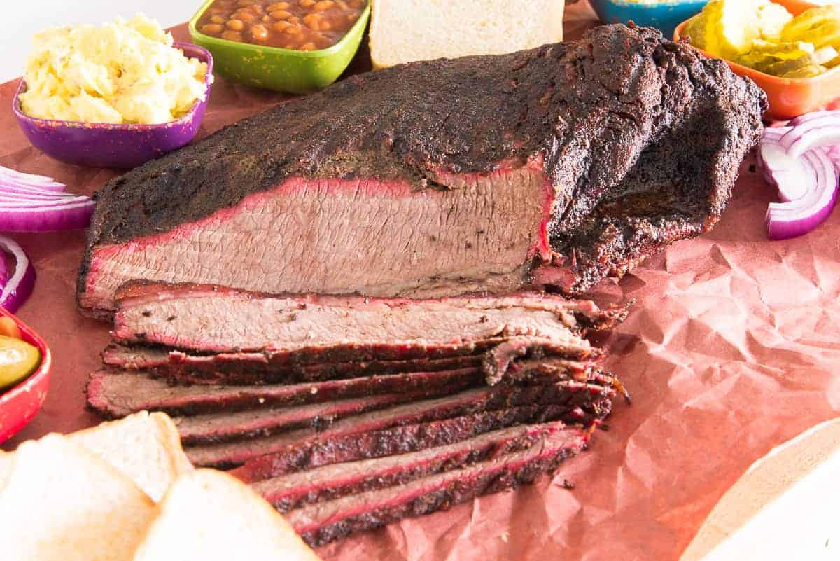 The partially sliced brisket is surrounded by sides and condiments
