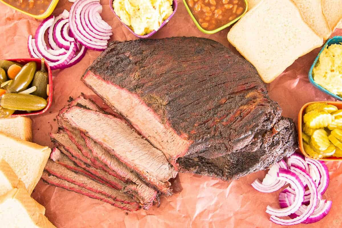 Overhead image of a partially sliced Coffee-Rubbed Smoked Brisket surrounded by sides and condiments.