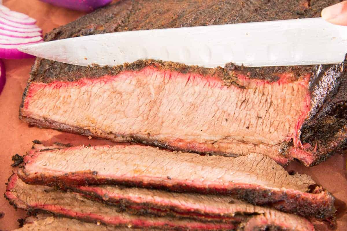 The brisket is sliced with a knife.