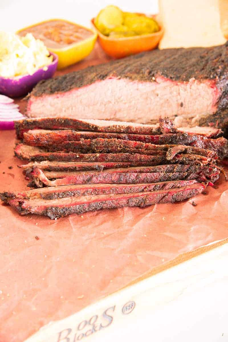 Portrait image of a Coffee-Rubbed Smoked Brisket partially sliced on a sheet of peach butcher paper