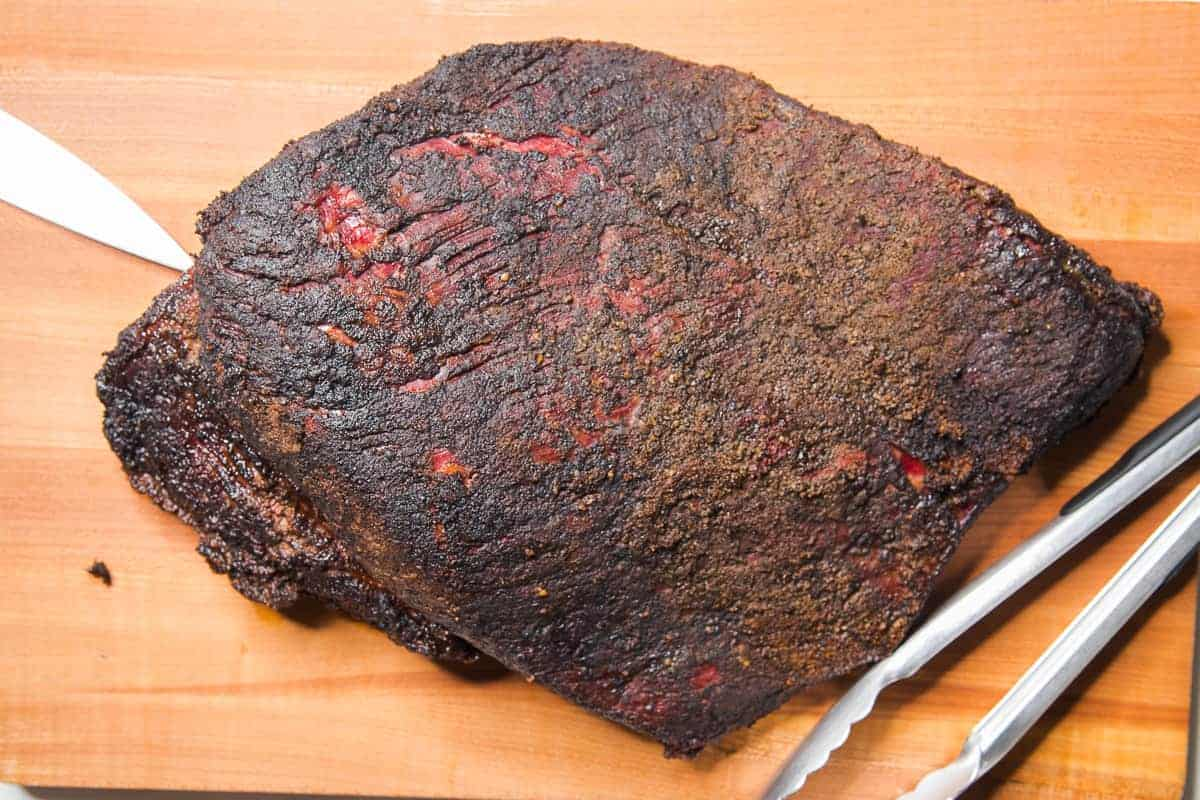 The smoked brisket on a wooden cutting board